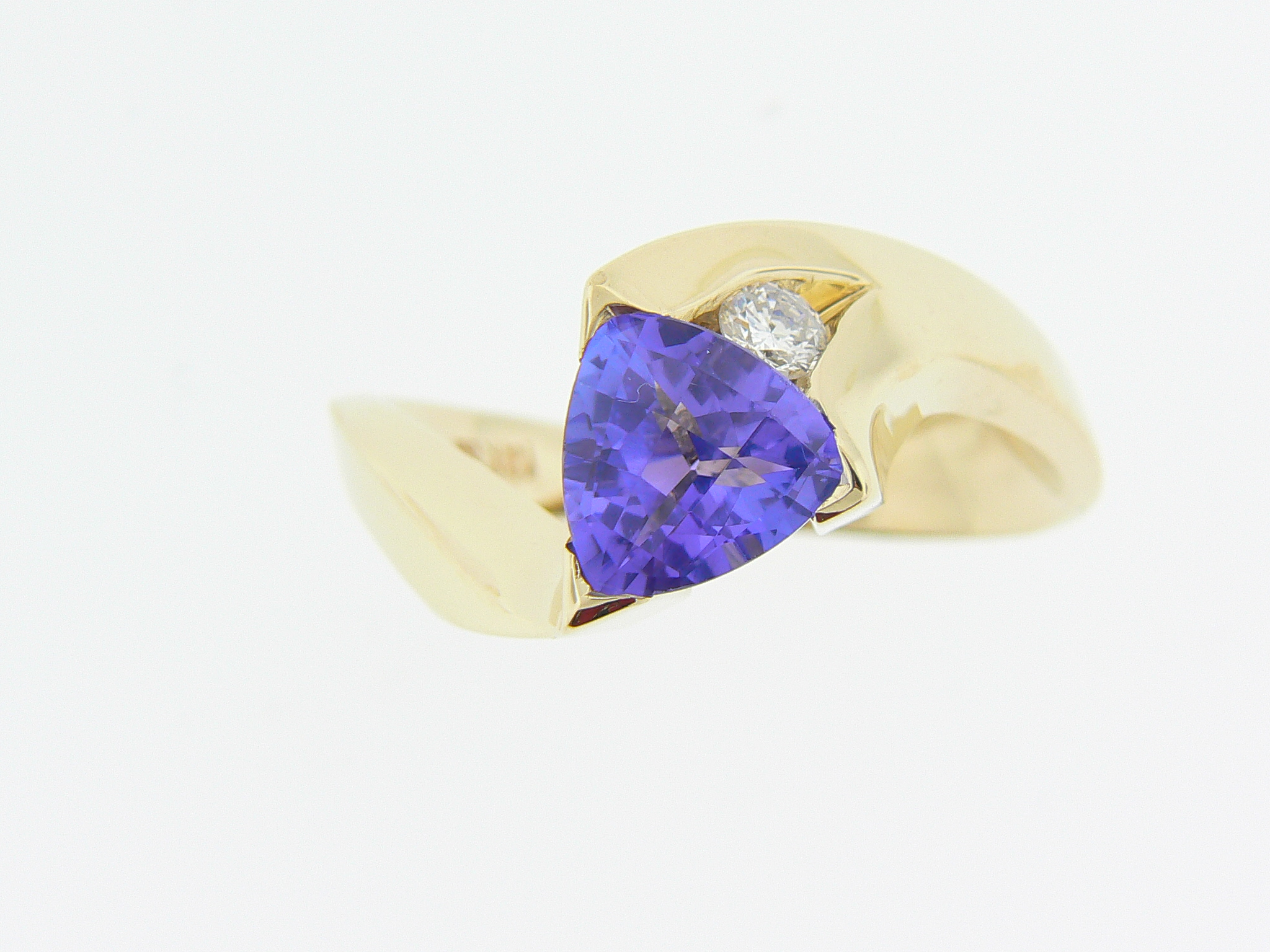 Tanzanite nested next to a diamonds set in 14KT yellow gold.